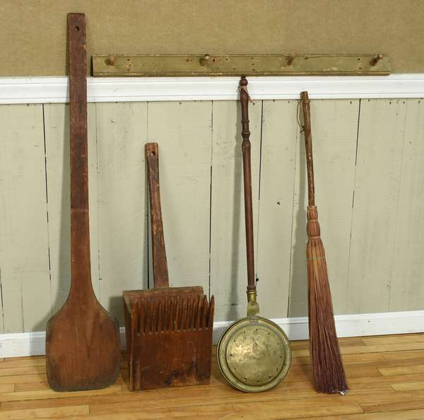 "Lot on country implements including early painted peg rack 41""L., brass bed warmer with turned handle, 43""L, bread peel, 50""L, country broom, 42""L, and a cranberry scoop, 33""L. Four pieces. Condition: expected wear"