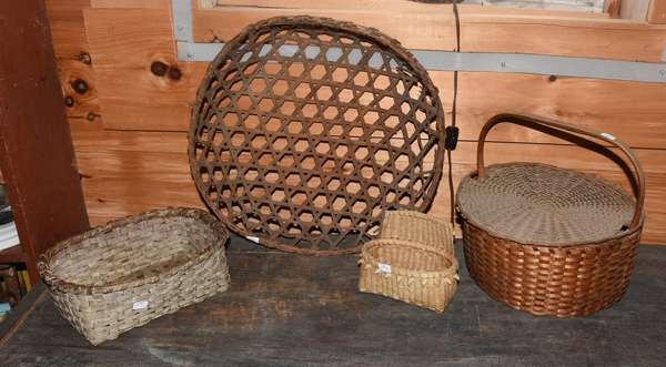"Lot of four early splint baskets, including lidded and handled basket with handle signed M.V. Sheahan, 11"" dia. x 10""H; a hexagonal open basket, 15.5"" dia; a rectangular basket in old white paint, 10""L x 7""W x 3""H; with a small hanging wall basket, 6""W x 4.5""H. Condition: breaks on hexagonal basket. Wear to paint on white example."