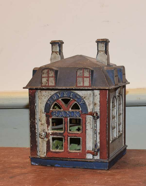 "19th C. cast iron mechanical bank, ""Novelty Bank"", bank building form, open the door and banker appears, early paint, 4.75""W x 4.75""L. x 6.75"