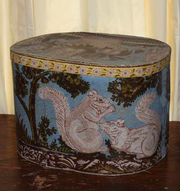 "Large 19th C. Wallpaper Hat Box, with squirrels on body, theorem basket and figures on lid, 12.5""W. x 16.5""L. x 12""H. Condition: unraveling to bottom and lid."