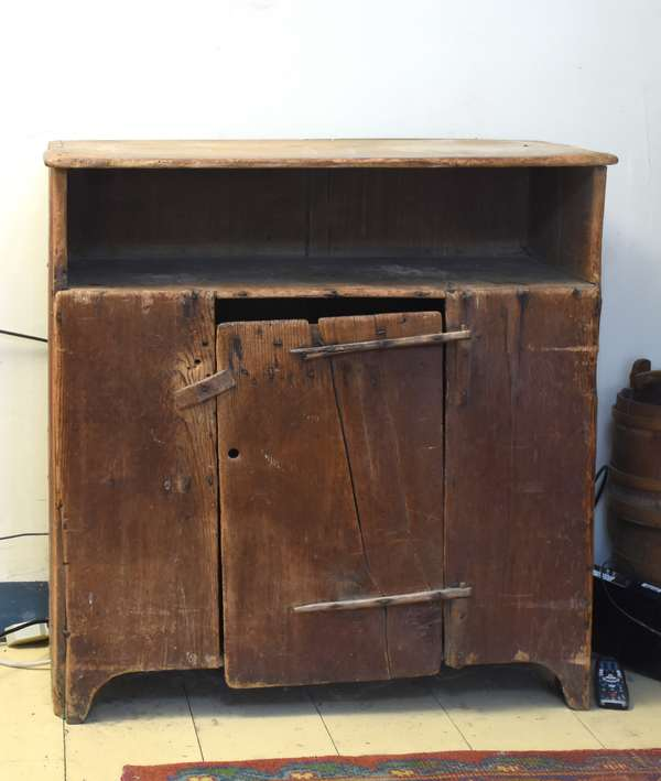 "Early 19th C. Primitive pine cupboard, open shelf above with unique hinged door below, on a cut put base. 37""W. x 39""H. x 16""D. Condition: shows 200 years of wear, once had upper shelving unit. Shrinkage and splitting to door."