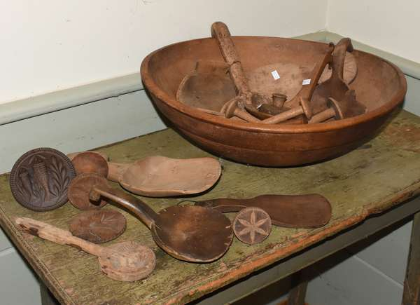 "Early chopping bowl with a collection of wooden ware, including butter stamps with thistle, fish,  and floral decoration, scoops, spoons, etc, 23 pieces, bowl 18 - 19.5"" dia. Condition: bowl with hole near lip, utensils worn, one butter stamp cracked, handle of burl spoon reattached"