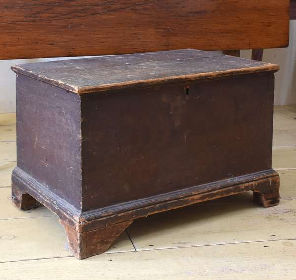 """Early 19th C child's size lift-top blanket box, in old brown paint on bracket feet, with unique hinged door on back side. 22""""L x 14""""W x 14.5""""H. Condition: shrinkage crack on lid, overall abrasions"""