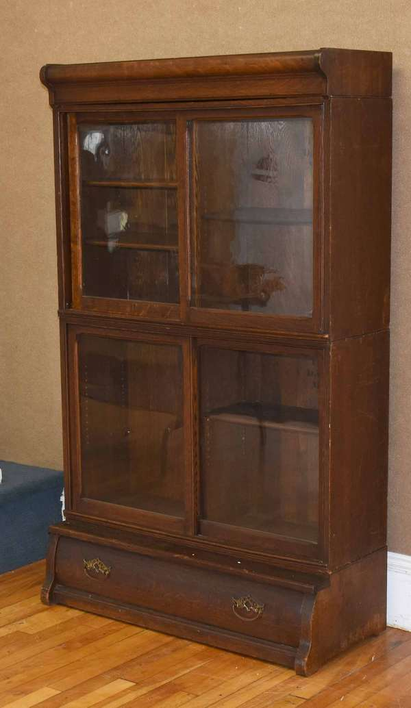 """Danner Trademark oak stacking barrister bookcase, 2 sections with sliding glass doors in 4 parts with drawer in lower section and separate cornice top, original finish, 62""""H X 37""""W X depth of bottom 16"""". Condition, structurally good no loss, some surface scuffs and drilled hole in top crest section."""