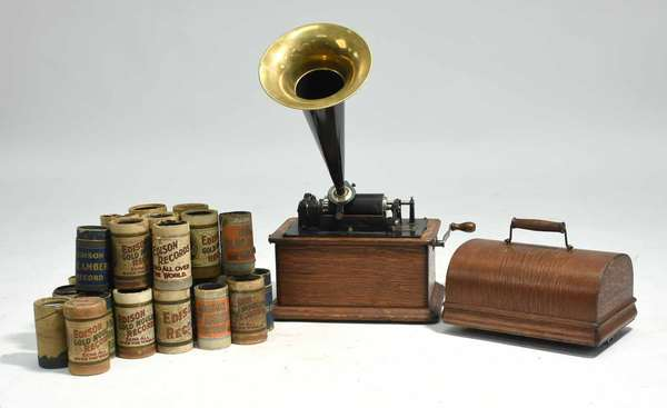 Edison Standard phonograph with original horn along with approx. 25 record rolls. Condition: old refinished oak case in good condition, horn in very good condition with no dents, some record rolls damaged