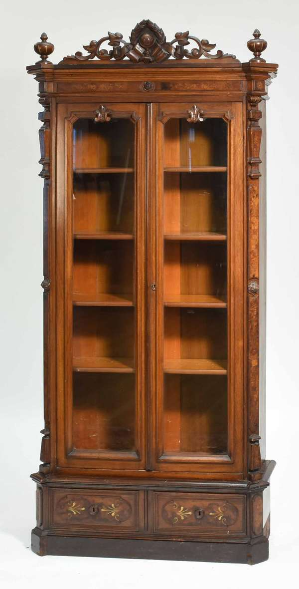 """19th C. carved Victorian mahogany bookcase with inlaid crest, two glass doors and two drawers on base 34""""W x 72.5""""H x 13""""D Condition; overall scuffing to base, glass in good condition."""