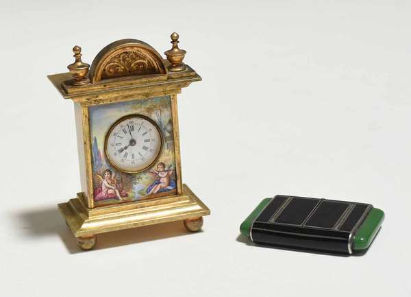 """Miniature Viennese hand-painted enamel and bronze mantle clock, scenes of putti playing instruments, 3""""H x 2""""W x 1.25""""D; with an Art Deco black and green enamel and sterling travel clock, face marked Tavannes, stamped sterling on inside, 1.75""""L x 1.25""""H. Condition: Art Deco with some craquelure to green, some scratching."""