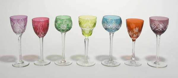 """Set of seven cut overlay colored wines, various shapes, colors including aqua, limes, cranberry and purple. 7.5""""H - 8.25""""H. Condition: very good, no chips or cracks, some scratching"""