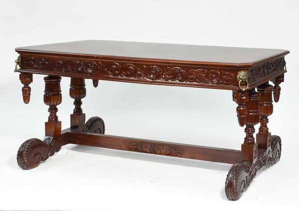"""Carved mahogany library table with trestle base, brass lion handles and drop finials at cut corners, with two drawers, 20th C. 32""""H x 35""""W x 63""""L. Condition: two small orange stains to top, some scuffing"""