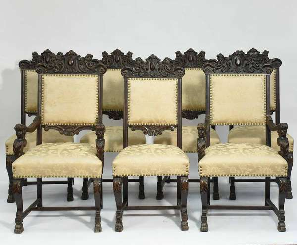 """Set of seven carved mahogany Horner chairs, with two arms, crest with putti and oval cartouche, arms with figural supports. Studded brocade upholstery. 44.5""""H overall, seat height 19""""H, width of armchair 24""""W, width of aide 20""""W. Condition: some scuffing"""