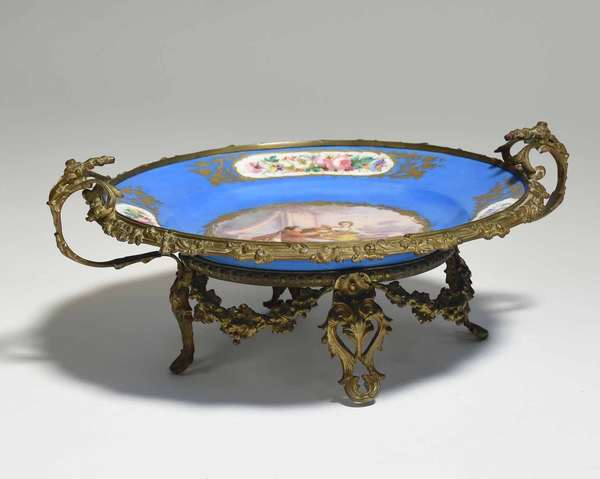 """19th C. bronze ormolu mounted Sévres Bleu Celeste porcelain centerpiece, hand painted decoration including center roundel of two lovers in garden. 17""""W x 7.5""""H, charger 13"""" dia. Condition: wear to gilding around rim of porcelain"""