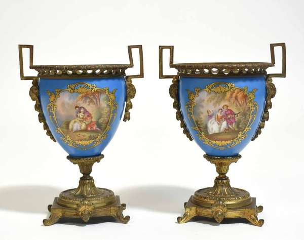 """Pair of Sévres bronze ormolu mounted urns with hand painted courtship and chateau scenes. 10""""H x 7""""W. Condition: one urn crack where mount attached on side, decoration in good order"""