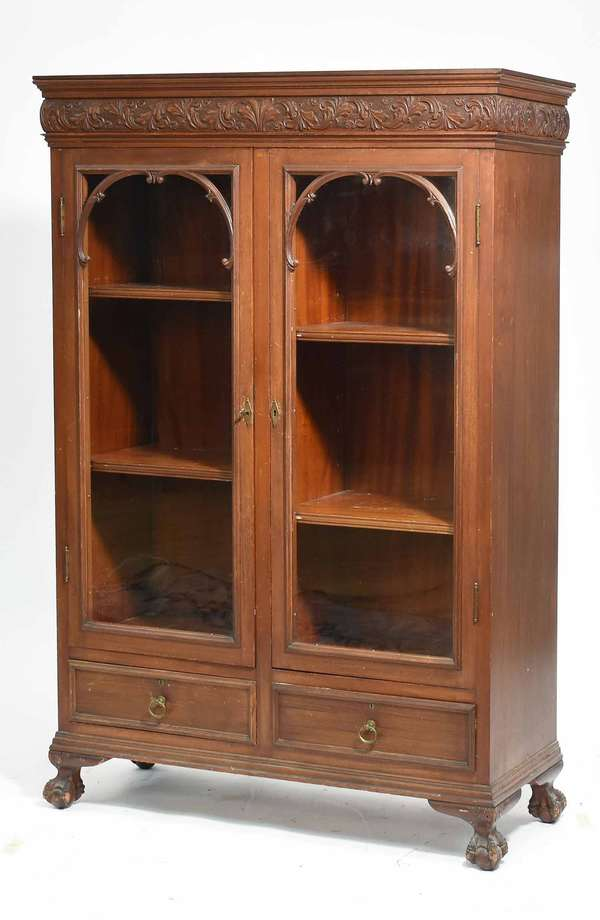 """Victorian carved mahogany bookcase, acanthus leaf cared frieze above two glass doors and two drawers, on claw and ball feet. 38.5""""W x 15'D x 53.5""""H. Condition: good, some scuffing"""