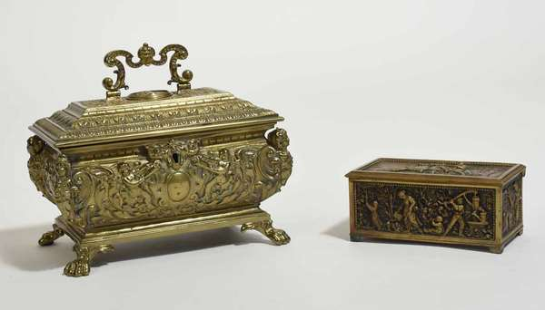 """Two 19th C. elaborately cast brass boxes, one example with hinged lid and embossed scenes of pastoral life, 5.5""""L x 3""""W x 2.75""""H; along with a footed casket shaped box with hinged lid, gadrooned edge and Mannerist motifs, both stamped with makers marks, 8""""L x 5.5""""W x 6""""H. Condition: very good"""