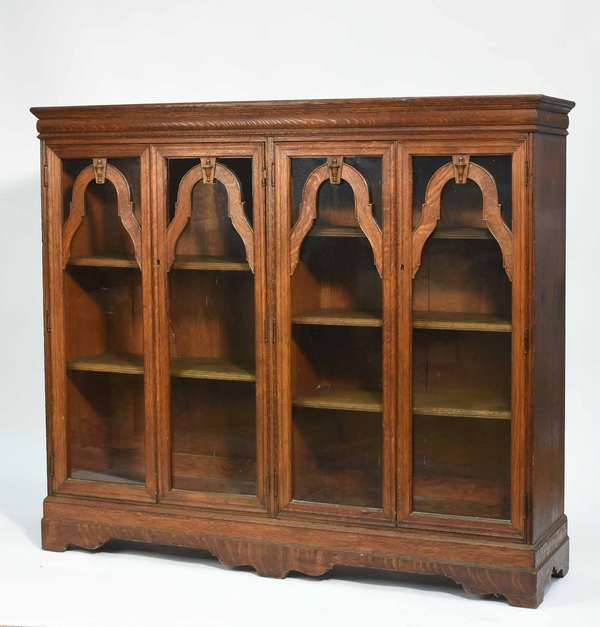 """Four-door Victorian oak bookcase with glass doors, interior shelves, on a bracket base. 63""""L x 54.5""""H x 15.5""""D. Condition: loss to front decoration on one door, to bottom of other, overall scuffing"""