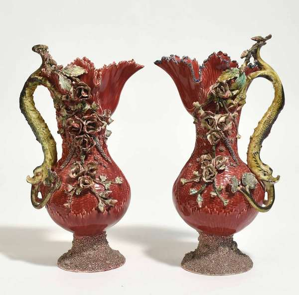 """Pair of French majolica ewers with dolphin form handles and applied floral decoration, 18""""H x 8""""W. Condition: some losses to petals and edges"""