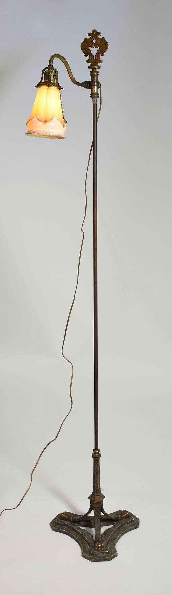 """Bronze floor lamp in a tri paw footed base, with an art glass shade, both unsigned, shade 5.75""""L, overall 65.5""""H. Condition: very good, some scuffing to top of shade, no other damage"""