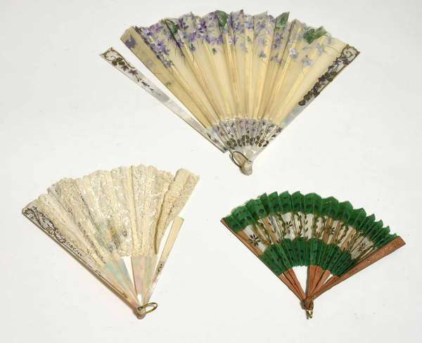 """Three antique French fans, including larger example with mother-of-pearl monture and hand painted violets on fabric, 13.75""""L; other with mother-of-pearl monture and lace leaf with drawing on paper of courting couple in center, 9.5""""L; and a small wooden and green fabric example, 7.5""""L. Condition: on large example mount has come off, two ribs broken, lace example with broken mount and six broken ribs; green example with some broken ribs"""