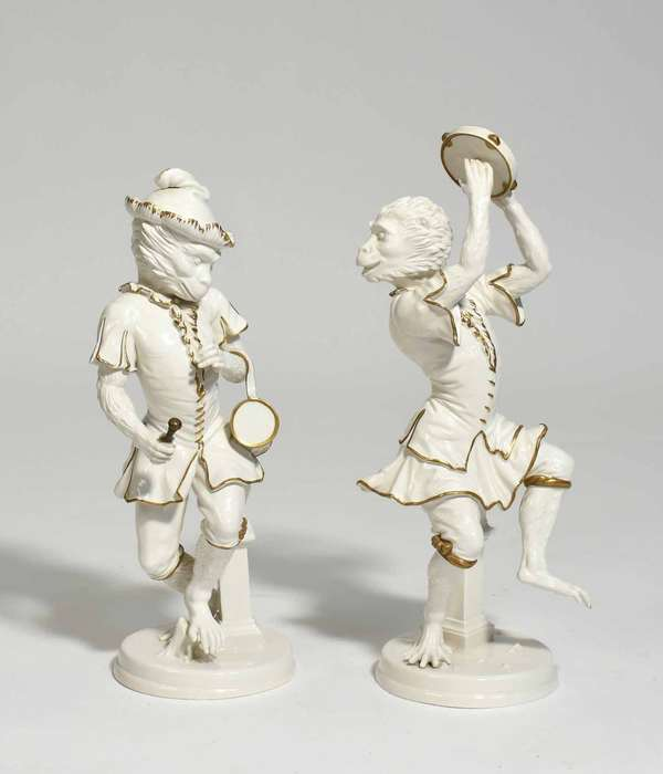 Pair of Mottahedeh style porcelain monkeys playing instruments, stamped on bottom made in Italy. Condition: craquelure, one missing plume to hat and thumb