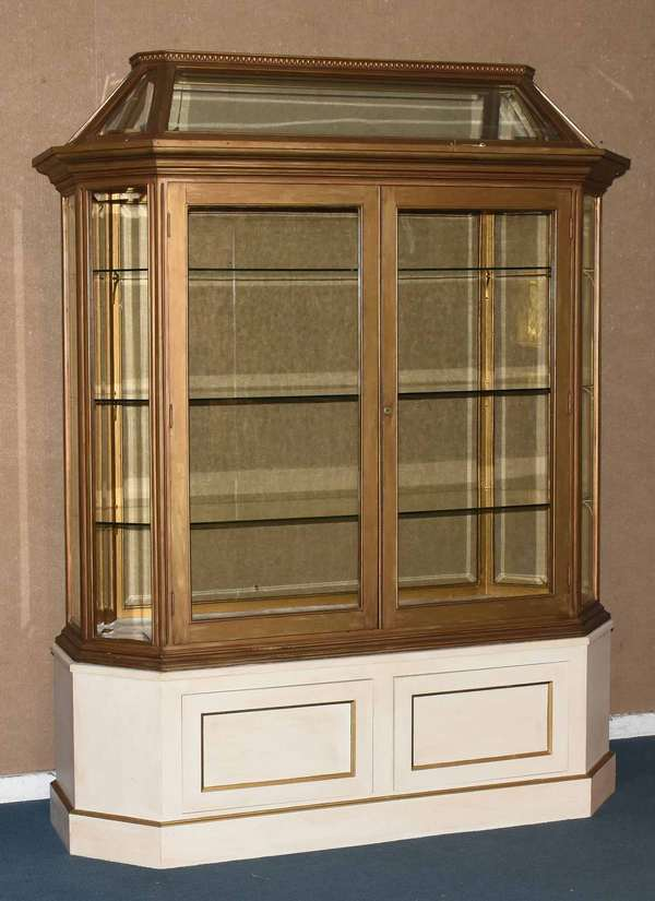 """Art Deco wooden display case with beveled glass panes and shelves, on a white wooden base, 80""""H x 64""""L x 27""""D. Condition: glass in good condition, wood with some scuffs"""