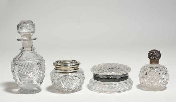 """Four cut glass items, including an 1830s American cut glass decanter, 9""""H, lidded box 5"""" dia., perfume with sterling cap, 4.5""""H, and a lidded jar with sterling top, 3.5""""H. Condition: one chip to rim, one chip to foot and come chipping to decoration of decanter"""