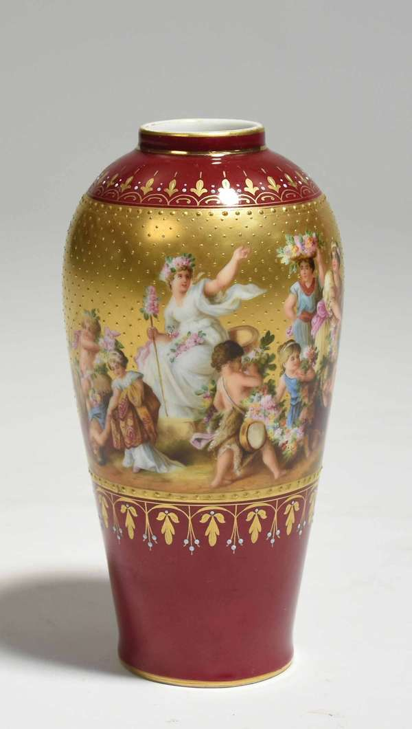 """Royal Vienna hand painted porcelain vase with a Classical bacchanal scene atop a maroon and gilded ground, ca. 1900, 6.25""""H. Condition: gilding to top lip worn"""