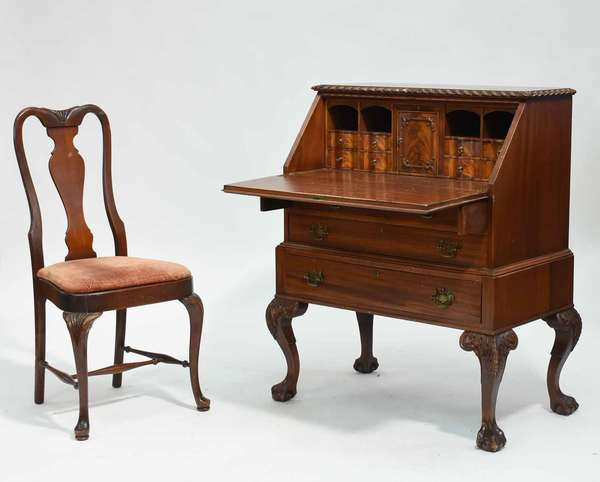 """Carved mahogany slant lid desk, with gadroon carved top edge, interior with carved doors, with two over three drawers below, and cabriole legs with acanthus carving on claw and ball feet. 33.5""""W x 20.25""""D x 41.5""""H. With a Queen Anne style side chair with carved knees, 18"""" seat height x 38""""H overall. Condition: loss to top edge of slant lid, wear to interior surface, scuffing to legs. Interiors of drawers with staining. Scuffing to knees and other areas of chair"""