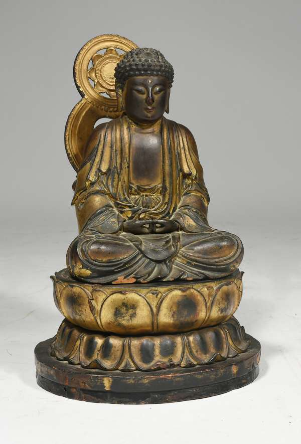 """19th C. Chinese carved and gilt wood Buddha on lotus leaf stand, very detailed carving of Buddha seated with legs crossed free standing on a lotus leaf base, original patina, 14""""H x 8.5"""" W. Condition Buddha has some gilt loss and chips to edges, halo behind repaired."""