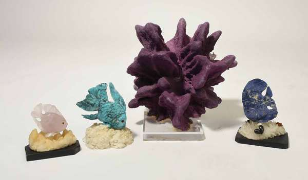 """Three unique carved fish sculptures along with a purple coral mounted on lucite base. Fish carved from sodalite, rose quartz and turquoise mounted on crystalline and black marble bases, 4.5"""" H - 6"""" H, purple coral group 12"""" H, 4 pieces, Condition: some roughness on top of fish, coral glued to lucite base -"""