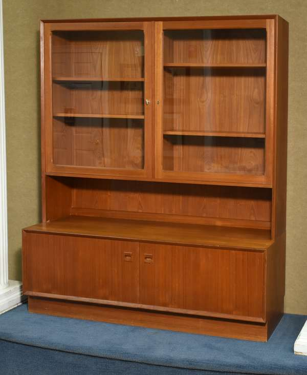 """Brover Danish teak wood hutch, two part, with two glass doors above, and two doors below, 53.25""""L x 19.5""""D x 64""""H. Condition: some scuffs to surface, flaking veneer on bottom of top section."""