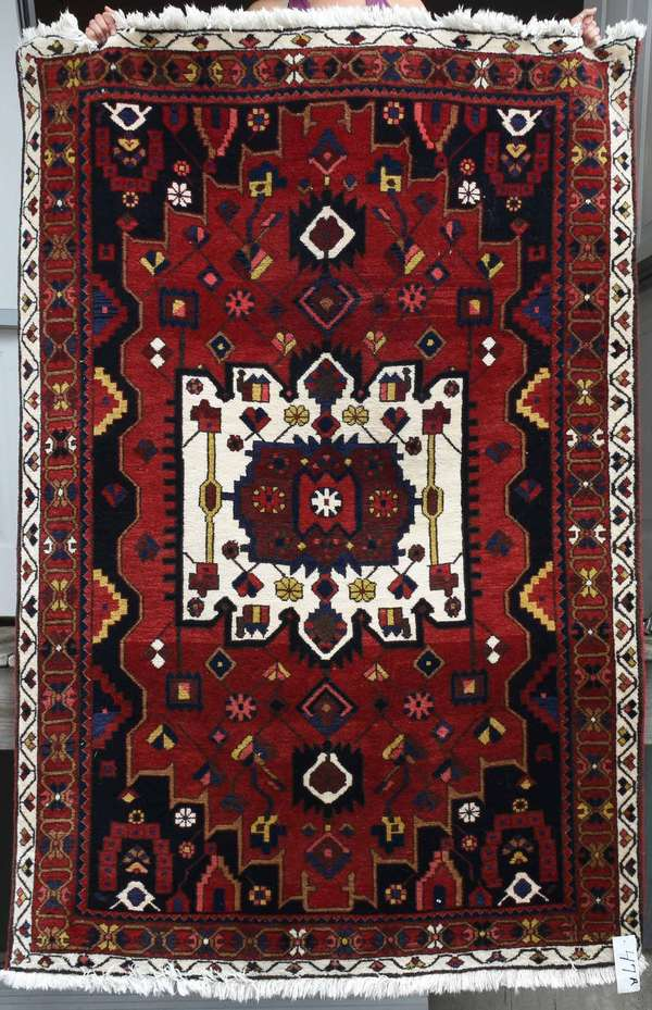 """Open field Iranian scatter rug with central ivory medallion, 6'8"""" x 5'. Condition: some bleeding of reds, overall good."""