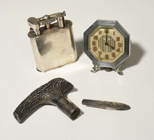 Lot of antique sterling, including a Deco era Waltham alarm clock, sterling cane handle, Gorham sterling pocket knife along with a silver plated Dunhill table lighter, four pieces. Condition: denting on cane handle, tarnishing and minor scuffing.