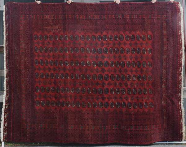 """Room size Bokhara rug, 10' x 12'7"""". Condition: seven professionally repaired small tears to center, full pile."""