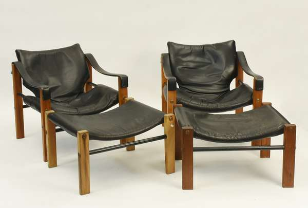 """Pair of vintage teak and black leather sling armchairs with ottomans. 24.5""""W x 26""""H Condition: Wear and creasing to leather, no rips. Sun fading to wood on one ottoman."""