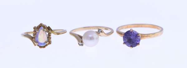 Three 14K gold rings, including opal, cultured pearl and purple stone. Condition: good.