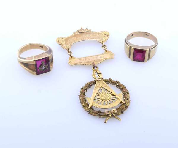 Two 10k gold class rings set with red stones, 16 grams, with a masonic 10k gold medal weighing 14 grams. Condition: good