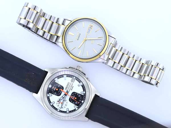 Two Seiko men's wrist watches chronograph with original black Seiko band with a dress watch, stainless with gold highlights