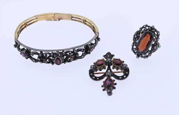 """3 pc. Victorian silver over gold, diamond and garnet suite. Consisting of a hinged bangle bracelet, approx. 7"""" inner circumference, set with old mine cut diamonds and garnets with hallmarks. A matching garnet ring, size 5, 7.95 x 15.43 mm surface, with hallmarks. 3rd piece in suite is a matching pin or pendant, also set with garnets and diamonds and hallmarked. Condition: overall good,bracelet missing small dia. some wear. New bidders to Smith's, payment for this lot must be made with cash, bank approved check or wire transfer.  NO CREDIT CARDS accepted as payment for this lot."""