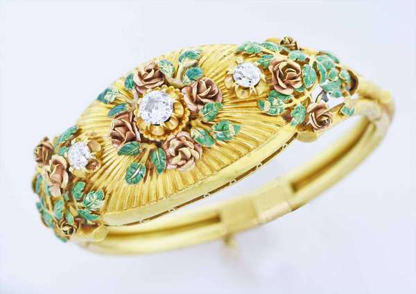 Antique beautifully made 18k yellow gold and diamond hinged bangle bracelet, accented by rose gold roses with green enamel leaves, approx. 1.0 ct J-I1 Old European (OE) cut diamond center, two side diamonds approx. .50 ct. J-K-VS-I each OE cut, approx. 1 1/4 in. wide, 53.1 grams, tested 18K gold. Condition: some wear to enamel clasp and double hinge, mechanisms work well. New bidders to Smith's - payment for this lot must be made with cash, bank approved check or wire transfer.  NO CREDIT CARDS accepted as payment for this lot.