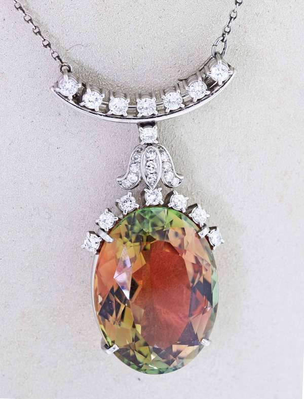 Andalusite and Diamond platinum pendant/brooch, with removable chain accented by approx. 1.0 ct. tw. round brilliant cut diamonds. Andalusite is approx. 43.8 ct., (one of the few gems with eye visible pleochroism-orange and green) pendant is 2 in. long, 16 in. long, 27.3 grams.  Condition; very good, minor nick to one facet of andalusite stone.   New bidders to Smith's, payment for this lot must be made with cash, bank approved check or wire transfer.  NO CREDIT CARDS accepted as payment for this lot.