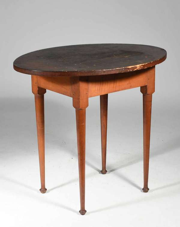 """18th C. New England tavern table, oval pine top with appealing old surface on turned maple legs ending in delicate button fee with traces of earlier red paint on base, 27.75""""H x top 31.5"""" x 24"""". Condition: overall very good, top with early surface showing good use, base once in red likely cleaned many years ago but maintains hints of the early color."""
