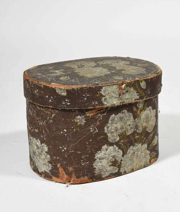 """19th C. Hannah Davis hat box, oval wood form with floral wall paper covering, news paper lined interior dated 1839 with a label of Hannah Davis - Jaffrey NH, 8.5"""" H x 12""""L x 9""""D. Provenance, Reinhold/Tolman estate. Condition: shows wear areas of wall, paper loss, edge west structurally good."""