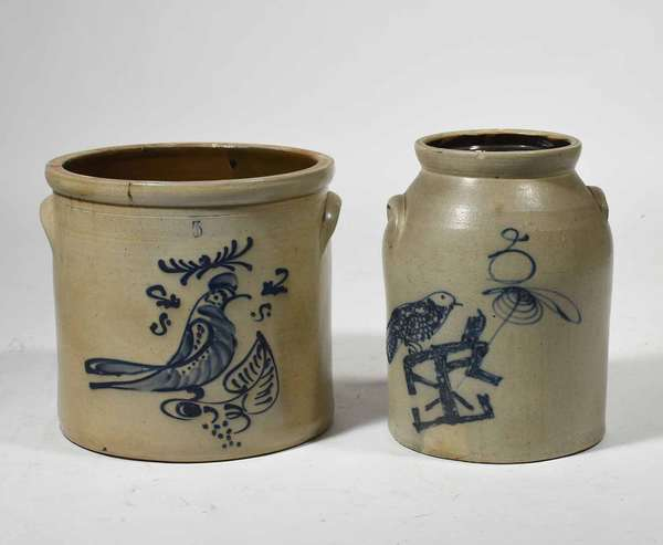 "Two 19th C. stoneware crocks; 5 gallon example with 2 handles and cobalt blue decorated bird and leaf design, 12""H x 13"" D, and a similar example with a bird perched on an unusual structure, 13.5""H x 11""H.  Condition: 5 Gallon example has 2 age cracks other minor flaking to blue design and a small chip to rim."