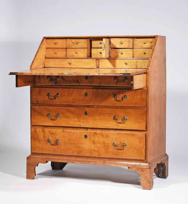 """18th C. New England curly maple slant lid desk, with a figured maple exterior and 4 drawers on it's original dovetailed bracket base, step down interior with dovetailed drawers and prospect door, 42"""" H x 35.75"""" W x 17.5""""D x 32"""" writing height. Prov. Reinhold/Tolman Estate. Condition: very pleasing older refinished surface, bail brasses replaced, structurally sound and ready for the home."""