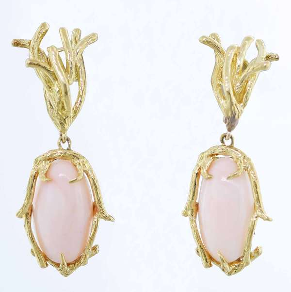 Angel skin coral earrings set in 18kt yellow gold, post style with 19 x 10 mm oval cabochons, approx. 2 in. long, (marked St. GEO), 17 grams.  Condition: good.  New bidders to Smith's - payment for this lot must be made with cash, bank approved check or wire transfer. NO CREDIT CARDS accepted as payment for this lot.
