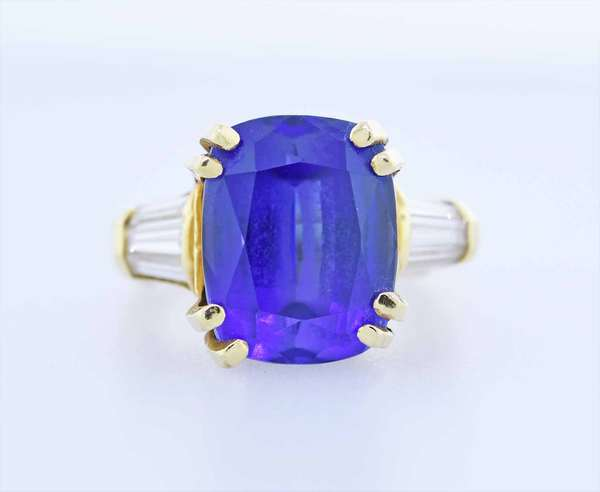 12 ct. Tanzanite ring. Rich electric blue color 12.12 carat tanzanite set in 18kt yellow gold accented by approx .50 ct. tw.  diamond baguettes, sz. 6 ring, 10.2 grams. Condition: very nice New bidders to Smith's - payment for this lot must be made with cash, bank approved check or wire transfer.  NO CREDIT CARDS accepted as payment for this lot.