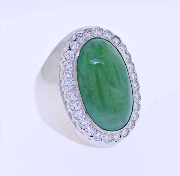 12 ct Jade ring set in white gold, approx. 12.5 ct oval green jade cabochon, accented by .75 ct. tw. round brilliant cut diamonds (G-VS), sz. 8 1/4, 13.9 grams. Condition; good. NOTE- white mark in photos on jade is a light reflection, it is not a mark on the stone.  New bidders to Smith's - payment for this lot must be made with cash, bank approved check or wire transfer.  NO CREDIT CARDS accepted as payment for this lot.
