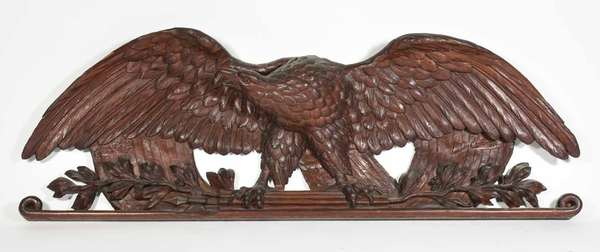 """Fine 19th C. American school carved walnut eagle,  depicting a spread winged eagle with branches and leaves, background carved imagery of the American flag showing Stars and Stripes, 13"""" H x 38""""L. Condition: repaired horizontal split, small areas of wear and loss, old finish."""