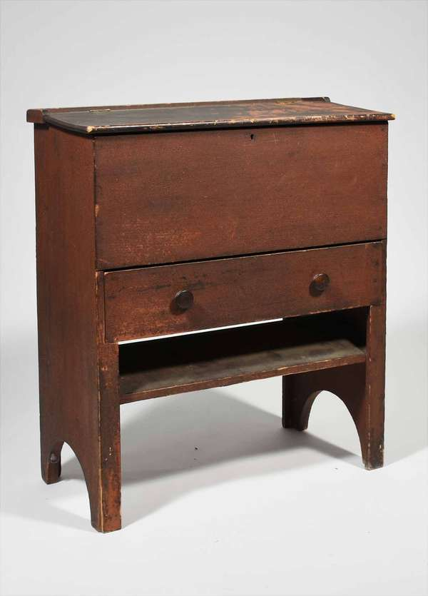 """19th C. Child's size standing desk in old red paint, likely Shaker,  a lift top revealing an open well,  long drawer below (nailed construction) and an open lower shelf for books, with half moon cut ends all in old red paint. 29""""H x 24""""W x 14""""D. Condition: structurally sound, no damage, paint wear and loss."""