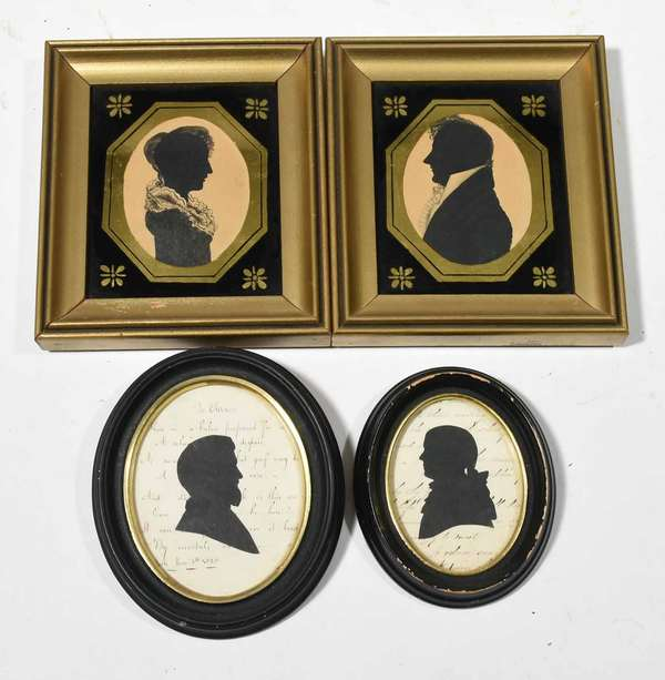"""19th C. Silhouettes, pair husband and wife hand painted and hollow cut on paper ovals 3.5"""" x 2.75"""" with reverse painted liners and gilt frames, overall size 7"""" x 6"""". With two other oval framed examples, black cut outs applied to scripted paper, overall size 5"""" x 4"""" and 6"""" x 5"""".  Condition: first pair appears frames are later and likely reverse painting, 2nd pair appears frames are later."""